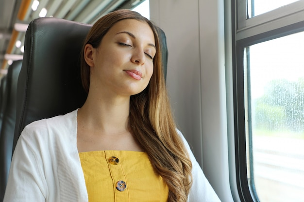 Tired business woman sleeping sitting in the train after a day of work . train passenger traveling sitting relaxed and sleeping.