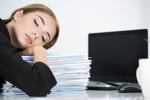 Tired business woman slleeping on heap of papers at her working place. overwork, working overtime and stress at work concept.