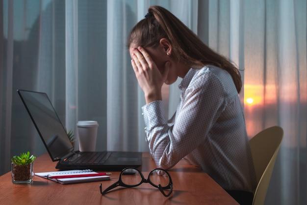 Устал бизнес женщина с головной болью, чувствую себя больным, несчастным во время напряженной работы над проектом.