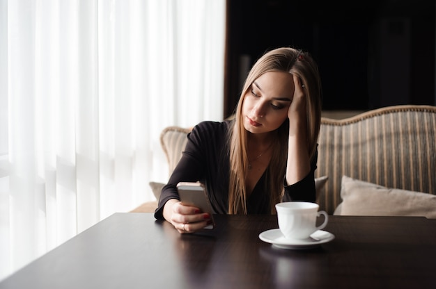休憩中に携帯電話で働く疲れたビジネスウーマン。