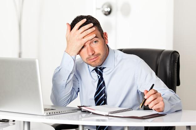 Усталый бизнесмен в офисе