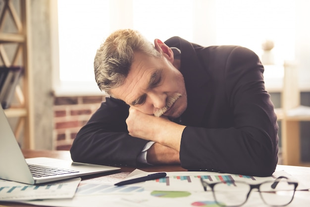 Tired businessman in classic clothes is napping on table.