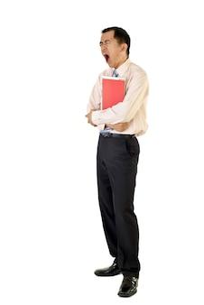 Tired businessman holding folders yawning on white wall.