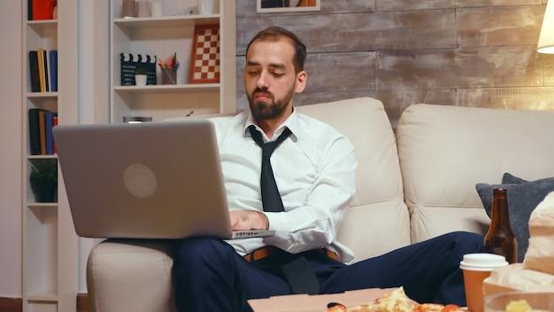Усталый бизнесмен в гостиной работает на ноутбуке и ест пиццу. предприниматель в галстуке.