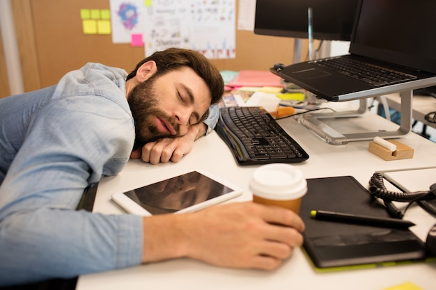 Tired businessman napping on desk in creative office