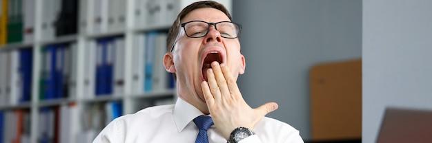 Утомленный бизнесмен офис сидит за столом и зевает. надежная и функциональная система управления финансами. человек откладывает работу дома во время самоизоляции. организационная работа офисного сотрудника