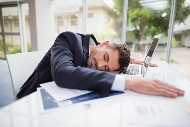 Tired businessman resting head on desk