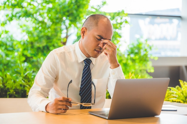 Tired businessman rubbing his eyes. office syndrome concept.