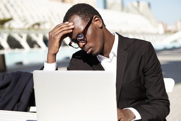 Усталый бизнесмен, сидя за столом на открытом воздухе, работая с ноутбуком