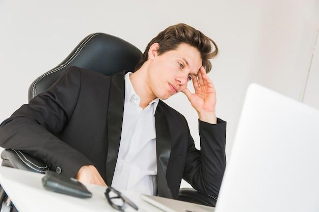 オフィスに座っている疲れたビジネスマン