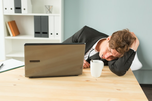 Tired businessman sleeping after hard working day in office interior