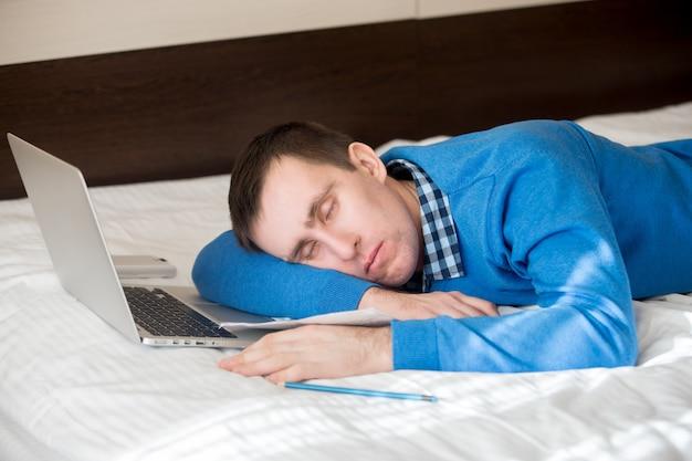 Tired businessman sleeping next to his laptop Premium Photo