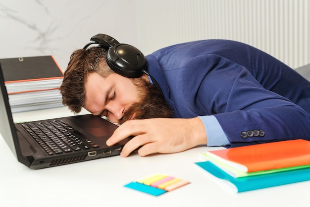 Tired businessman sleeping in office. bearded man sleeping at his working place.