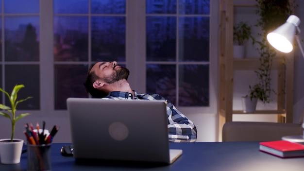 Усталый бизнесмен, спящий на стуле в своем домашнем офисе. переутомленный предприниматель.