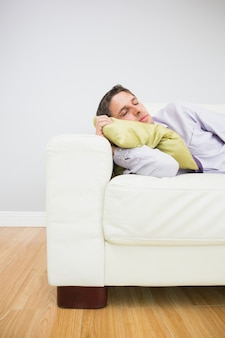 Tired businessman sleeping on sofa in living room