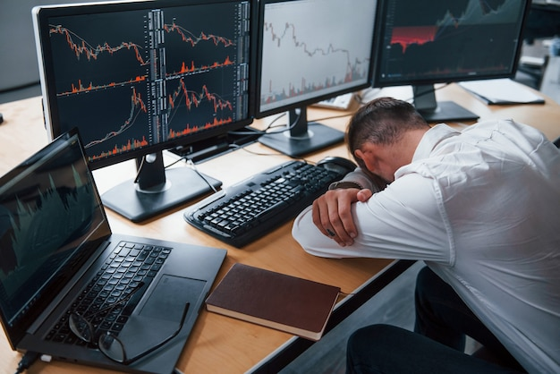 Tired businessman sleeping on the workplace by leaning on the table with multiple screens on it. stock information on displays.