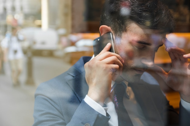 Tired businessman speaking on phone in cafe