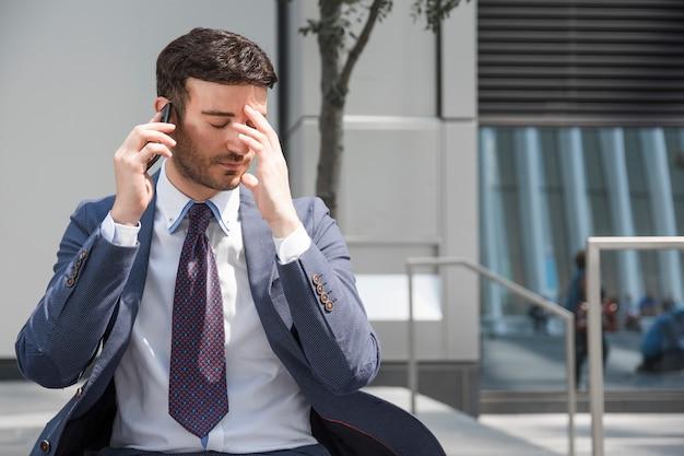 Tired businessman speaking on smartphone
