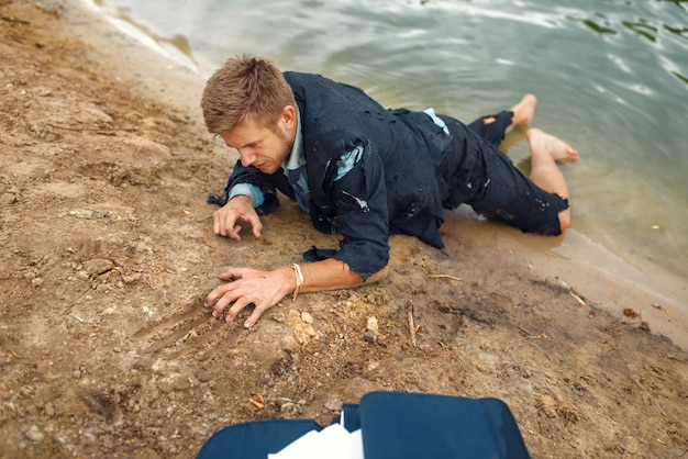 Tired businessman in torn suit trying to get out of the water on lost island.