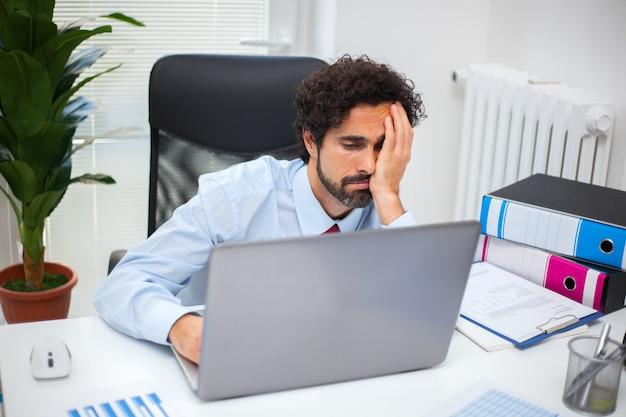 Утомленный бизнесмен работая в его офисе