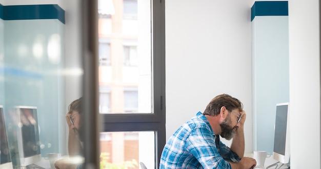 デスクトップコンピュータで作業している疲れたビジネスマン。頭を手にコンピューターを使用して成熟した男。ガラスのドアに取り組んでいるビジネスマンの反射。自宅で働く心配している実業家