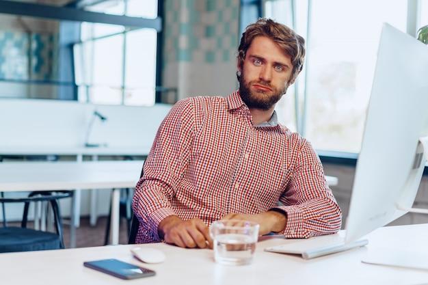オープンスペースのオフィスで彼のコンピューターに取り組んで疲れたビジネスマン。営業日の終わり