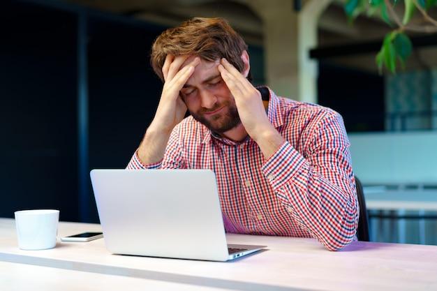 Утомленный бизнесмен работая на его компьютере в офисе открытого пространства. конец рабочего дня