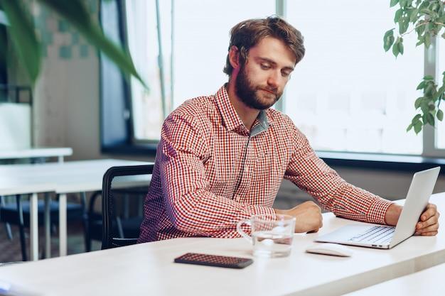 Утомленный бизнесмен работая на его компьютере в офисе открытого пространства