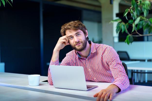 オープンスペースのオフィスで彼のコンピューターに取り組んで疲れたビジネスマン