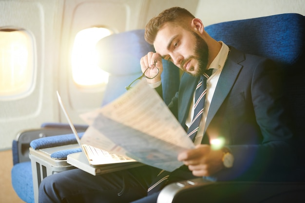 Tired businessman working in plane