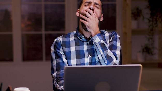 피곤한 사업가는 집에서 밤 시간에 노트북 작업을 하는 동안 하품을 합니다.