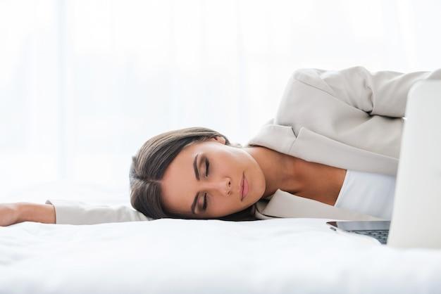 Усталая деловая женщина. красивая молодая деловая женщина в костюме спит, лежа в постели