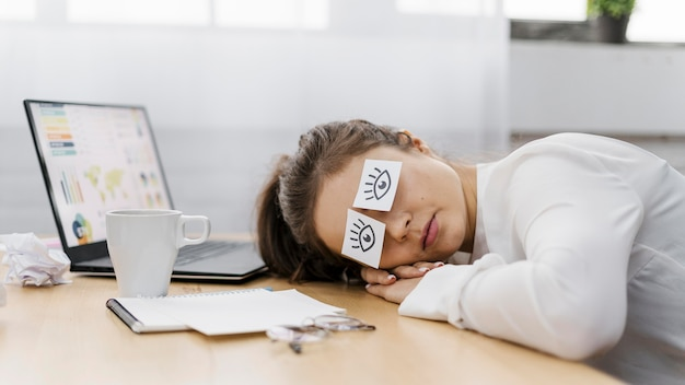 Tired businesswoman covering her eyes with drawn eyes on paper