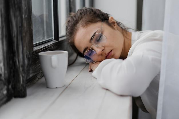 Donna di affari faticosa che riposa la sua testa su un davanzale della finestra