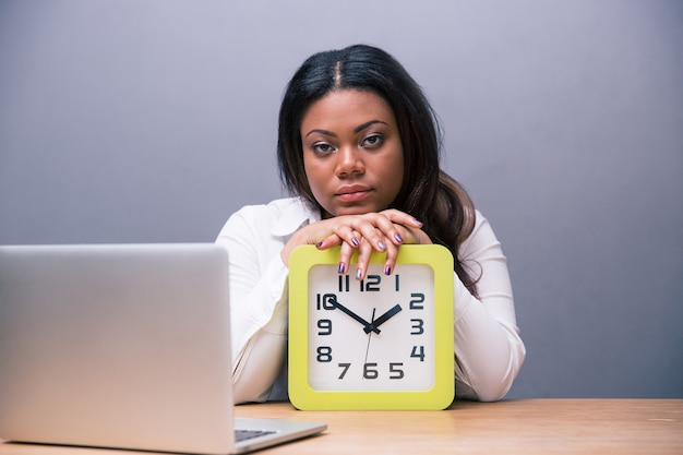 Tired businesswoman sitting at the table with clock