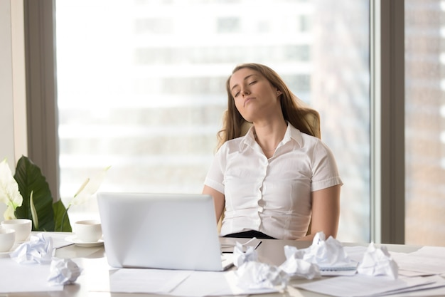 Tired businesswoman sleeping in chair at the desk