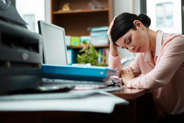 机の上で寝ている疲れた実業家