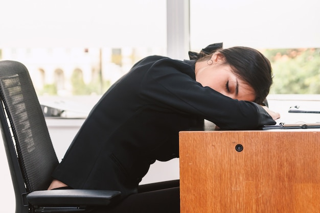 Tired businesswoman sleeping with laptop on the table at office
