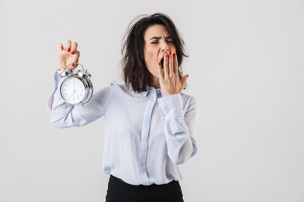 疲れた実業家は、白い壁の上に孤立して立って、目覚まし時計を示して、あくびをしているスマートな服を着ています