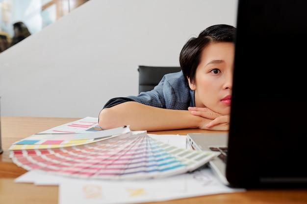 仕事でラップトップを使用して疲れている実業家