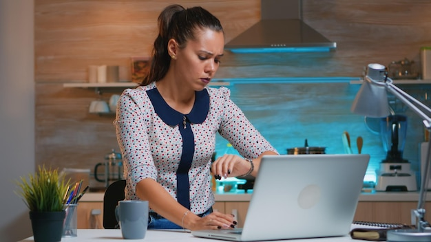 Tired businesswoman working overtime drinking coffee at home in modern kitchen. busy focused employee using modern technology network wireless overworking for job reading writing, searching.