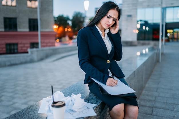 疲れた実業家は、屋外、財務諸表、ビジネスセンターで働いています。モダンな建物、街並み。女性実業家
