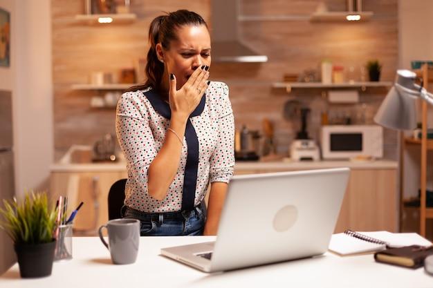 家庭の台所でラップトップを使用して締め切りに取り組んでいる間あくびをしている疲れた実業家。深夜に最新のテクノロジーを使用して、仕事、ビジネス、忙しい、キャリア、ネットワーク、ライフスタイルのために残業している従業員。