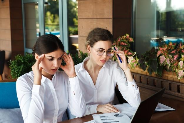 疲れたビジネスウーマンや頭痛のある学生。屋外のストリートカフェでラップトップを使用して美しい女性