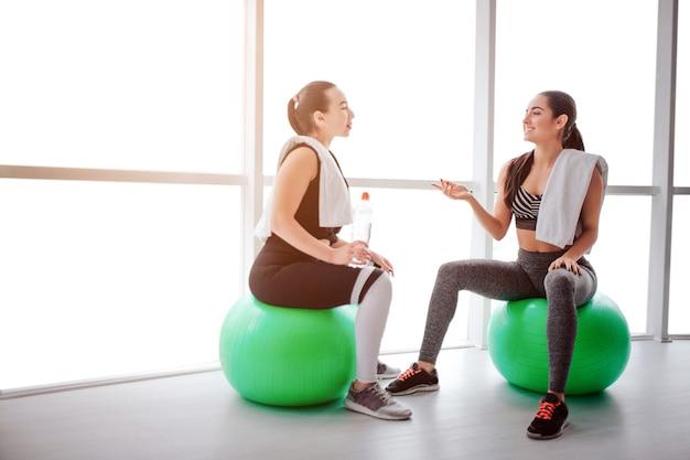 疲れているが幸せな若い女性がfitballsに座って話します