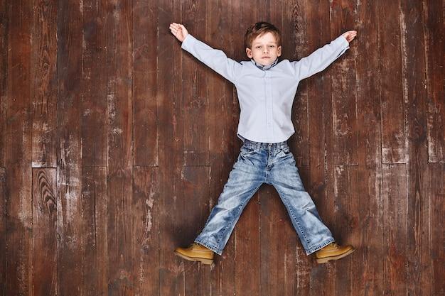 Усталый, но радостный мальчик растягивается, лежа на полу, глядя в камеру и улыбаясь