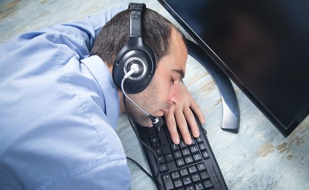 オフィスの机で寝ている疲れたコールセンターのオペレーター。