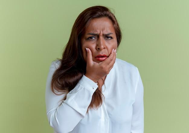 Усталая повседневная кавказская женщина средних лет схватилась за подбородок на оливково-зеленом