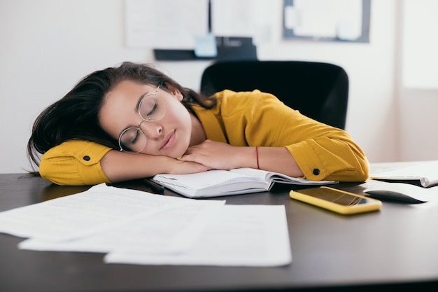Tired caucasian businesswoman in eyewear sleeping on desk while working