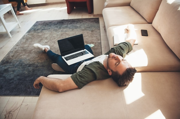 Tired caucasian man lying on floor with a laptop falling asleep after working online